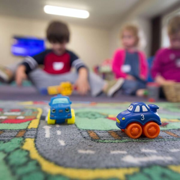 Blue Toy Cars on Play Mat with kids in background
