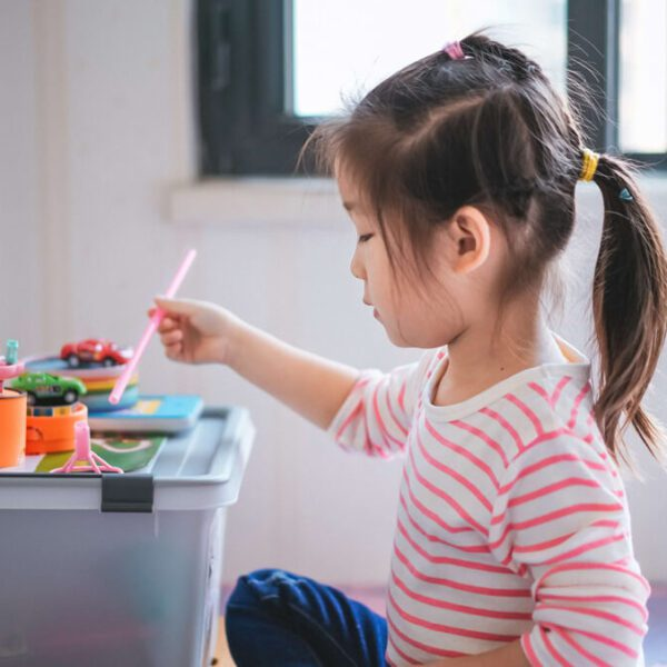 Little Girl in Pink Striped Shirt Playing with Toys on a Storage Tub